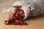 picture of sleeping bag  - Dried tomatoes got enough sleep from canvas bag at wooden background