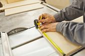 pic of workbench  - Worker with tape measure and pencil in a workshop measuring plywood at workbench and making marks on a product near saw on a router table - JPG