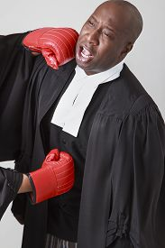 image of toga  - bald black man wearing canadian lawyer toga getting punch in the face and in the guts by a red boxing gloves - JPG