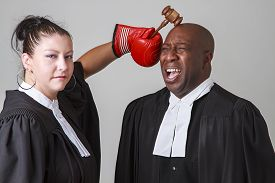 stock photo of toga  - woman hammering a man on the head with a gavel both wearing canadian lawyers toga - JPG