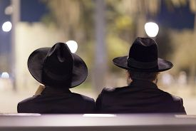 stock photo of israel people  - The silhouette of two Jewish men who are sitting on the bench - JPG