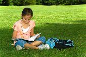 Young girl in park doing school work
