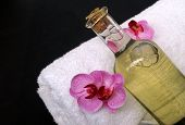 image of massage oil  - White bath towel and bath massage oil decorated with orchid blossom for a relaxing treatment - JPG