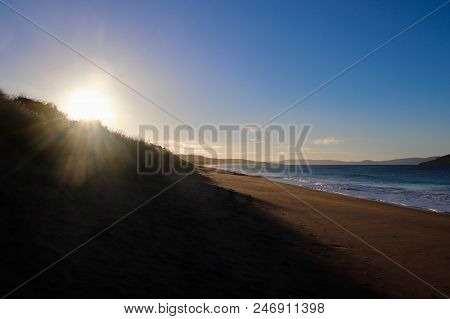 poster of Sunny Summer White Sandy Beach With Sun Rising In Distance, Clean Calm Ocean With Waves Breaking And
