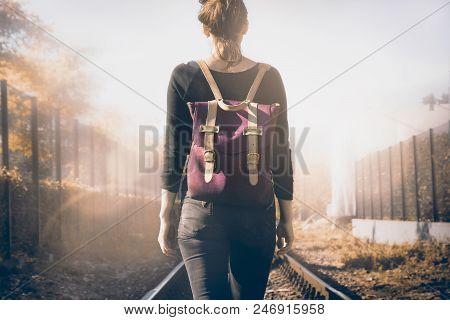 poster of Traveler girl walking on railway tracks. Lonely traveler girl. Traveler. Traveler girl walking in sunshine. Travel concept. Backpack traveler.