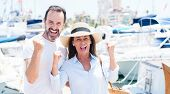 Middle age couple in marina screaming proud and celebrating victory and success very excited, cheeri poster
