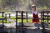 Pretty Small Blond Long Haired Girl In Nice Red Dress Stands Alone On Old Cement Bridge Leaning On W poster