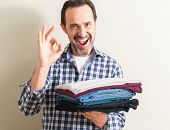 Senior man holding folded laundry clothes doing ok sign with fingers, excellent symbol poster