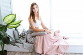 Relaxed Young Woman Enjoying Relaxing On Comfortable Sofa, Near A Large Window, Calm Attractive Girl poster