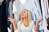 Overwhelmed woman picking clothes and sitting in a wardrobe