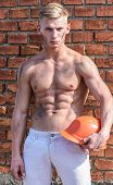 Builder With Muscular Torso And Helmet, Brick Wall On Background. Athlete With Sexy Nude Torso With  poster