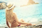 Fashion Woman In Summer Hat Relaxing On The Beach. poster