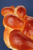 baked product : golden challah on blue wooden table