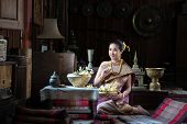 Beautiful Thai Girl In Traditional Dress Costume Sitting At Ancient Wooden House,thai Woman In Tradi poster