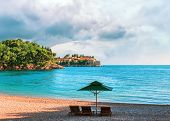 Lounge Chairs And Umbrella On The Royal Beach At Adriatic Sea In Montenegro, View To The Sveti Stefa poster