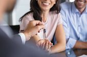 Close up of man hand giving house keys to woman. Smiling mature woman receiving new house keys from  poster
