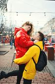 Young Romantic Couple In Love Hugging, Wearning In Bright Yellow And Red Down Jackets. Handsome Man  poster