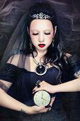 Young beautiful gothic woman holding clock in her hands, on vintage grainy damaged background