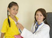Asian Doctor Examining Child