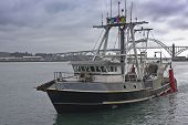 Fishing Vessel Returning To Port After A Days Work Newport Oregon. poster