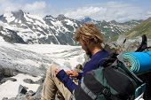 Tourist Looking To Map In Mountains poster