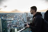 Portrait Of Young Man With A Camera On The Observation Deck Enjoying The Panorama Of Frankfurt. Germ poster