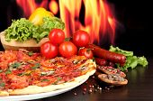 delicious pizza, salami, vegetables and spices on wooden table on flame background