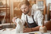 Attentive Stonemason With Stylish Beard In Protective Goggles Detailing Creative Sculpture Of Woman  poster