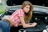 The beautiful girl repairs the car