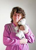 stock photo of teddy-bear  - a beautiful senior lady hugging her valentines teddy bear - JPG