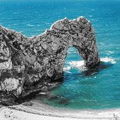 Durdle Door Rock Arch. Lulworth On The Dorset Coast In Southern England. With Desaturated Rock And B poster