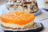stock photo of cheesecake  - Tangy colourful citrus cheesecake with a vivid orange topping over a creamy cheese filling displayed on a buffet table of assorted cakes for dessert - JPG