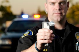 foto of police  - A police officer holding a breath test machine with his police car in the background - JPG