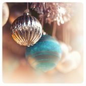 Detail of christmas baubles with tinsel. Selective focus and bokeh background. Cross-processed with pastel shades, to create a retro instant photo effect.