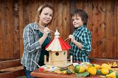 Woman and her son painting a bird house with vivid colors