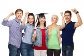 education and people concept - group of standing smiling students with diploma and corner-cap