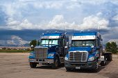 Two Typical American Blue Freightliner Trucks On A Parking Place Before Heavy Storm