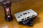 image of magnetic tape  - Hourglass and cassette tape on the wooden table - JPG
