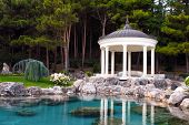 stock photo of gazebo  - gazebo by the pond in a beautiful green park - JPG