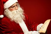 picture of letters to santa claus  - Portrait of Santa Claus looking at Christmas letter in his hands - JPG