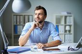Smart businessman thinking about something in office