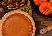 Overhead view of a fresh baked pumpkin pie ready for Thanksgiving. The pie is surrounded by autumn a