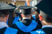 stock photo of rear-end  - Rear view of a group of graduate students on a ceremony - JPG