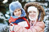 Happy friends kids in winterwear looking at camera outside