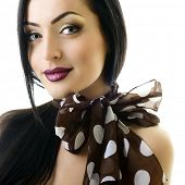 Young attractive woman with bow of neck-piece and nice makeup looking at camera, studio shot of pret