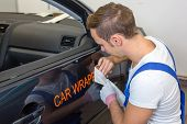 Car Branding Specialist Puts Sign With Car Wrapping Film On Automobile