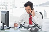 Young businessman writing notes while using land line phone at a bright office