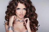 Beautiful Young Woman With Long Curly Hairs Isolated On Gray Background. Jewelry Accessories.