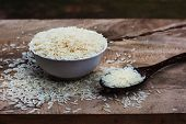 Rice With Wooden Spoon And White Cup On Wooden Table.