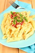 Rigatoni pasta dish with tomato sauce on wooden table close up